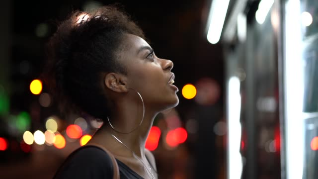 afro young woman looking for the news at newsstand - magazine publication stock videos & royalty-free footage