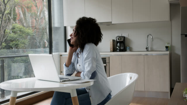 vídeos de stock e filmes b-roll de afro young woman receiving a call while working from home using laptop - afro