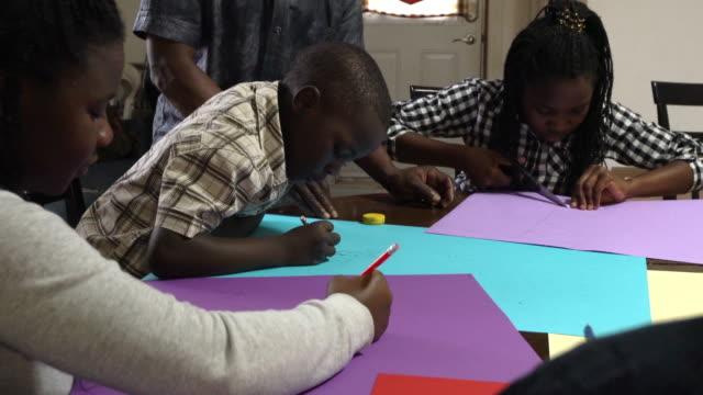 vídeos de stock e filmes b-roll de afro-american family paper craft home - família com quatro filhos