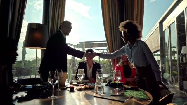 afro-american female manager greeting her colleagues at the business lunch in luxury restaurant - lunch stock videos & royalty-free footage