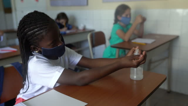 教室で手指消毒剤を使用したアフロ系の女性生徒。covid-19 コンセプト。 - 消しゴム点の映像素材/bロール