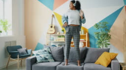 Afro-American girl in headphones dancing on sofa listening to music having fun