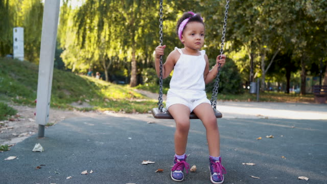 Afro-american girl swinging on a swing