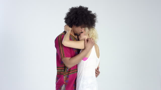 afro/asian love couple hugging and kissing - rotating on turntable