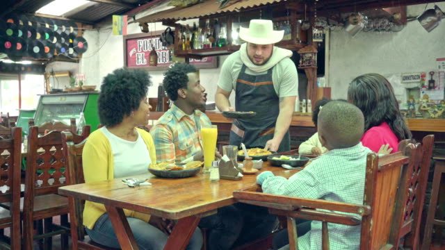 afro-colombian family, consisting of mother and father, grandmother and two children, a girl and a boy, appear sitting around a table in a typical colombian restaurant, eating typical food of the country. the video shows how a waiter attends the table whe - colombian ethnicity stock videos & royalty-free footage