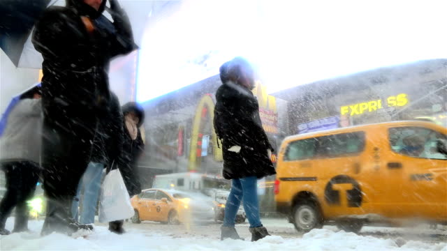 After a day of 60 degree Fahrenheit temperature winter storm Niko hits the Northeast of the United States / Rushour morning in Times Square Midtown...