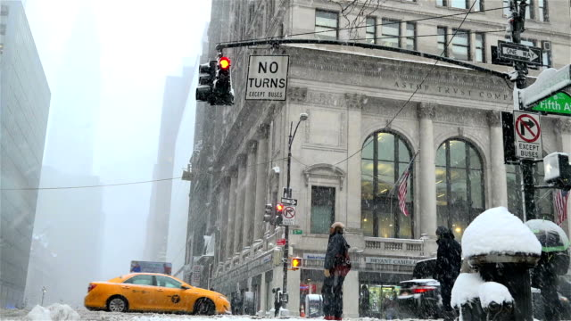 after a day of 60+ degree fahrenheit temperature winter storm niko hits the northeast of the united states / 5th avenue - 42nd street, midtown... - 42nd street stock videos & royalty-free footage