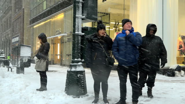 After a day of 60 degree Fahrenheit temperature winter storm Niko hits the Northeast of the United States / Midtown Manhattan New York City USA