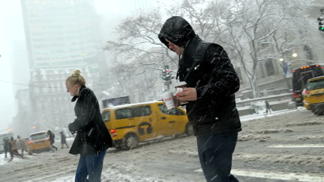 After a day of 60 degree Fahrenheit temperature winter storm Niko hits the Northeast of the United States / 5th Avenue 42nd Street Midtown Manhattan...