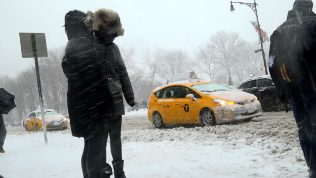 After a day of 60 degree Fahrenheit temperature winter storm Niko hits the Northeast of the United States / 5th Avenue and 59th Street Midtown...
