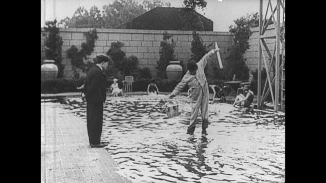stockvideo's en b-roll-footage met 1921 after a failed attempt at hunting, man (buster keaton) sees a man walking across a pool and tries to do the same but falls into the water - 1921