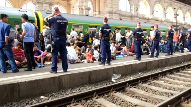 after a two-day lockout from keleti train station in central budapest, refugees are allowed in to board trains. police closely guard the train... - budapest stock-videos und b-roll-filmmaterial