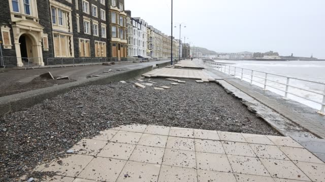 vídeos de stock e filmes b-roll de after a week of high tides, storm surges and storm force winds, the sea front promenade of aberystwyth in wales has been devastated, with millions of... - aberystwyth