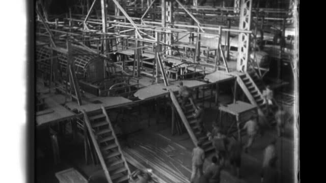 vídeos y material grabado en eventos de stock de after an air raid warning is lifted transport plane factory workers that include youth volunteers resume assembly tasks and wear divine-wind... - cinta de cabeza