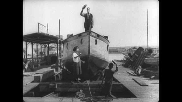 1921 after an unsuccessful boat naming ceremony, man (buster keaton) stands on the deck of his launching boat as it sinks below the water - 1921 stock-videos und b-roll-filmmaterial