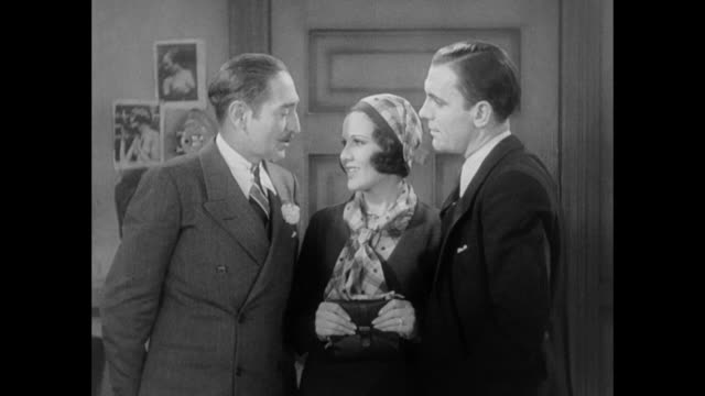 1931 after asking reporter (pat o' brien) for permission, editor (adolph menjou) kisses his new fiance (mary brian) - 1931 stock videos & royalty-free footage