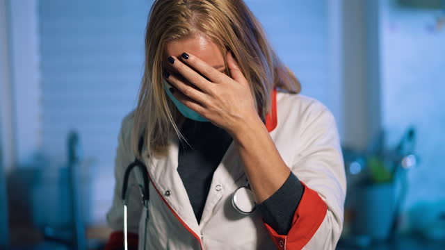 vidéos et rushes de after bad news female doctor in surgical mask feels broken - mauvaise nouvelle