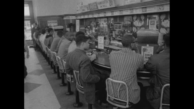 after being denied service during a sit-in demonstration, african american students remain quietly seated at a segregated lunch counter in... - lunch stock videos & royalty-free footage
