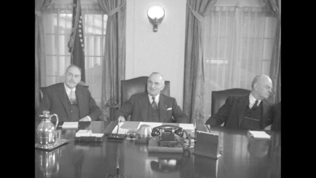After cabinet members have presented Pres Harry Truman with leather chair he used during his Presidency Truman and cabinet pose for photo op standing...