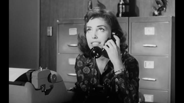 1959 after company owner (susan cabot) pays bill without question, concerned secretary calls executive - gereiztheit stock-videos und b-roll-filmmaterial