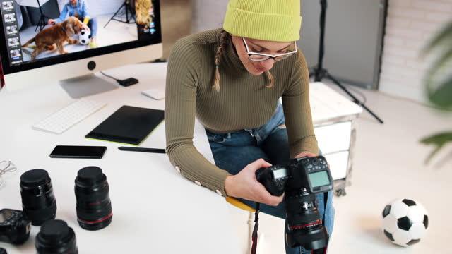 nach abschluss der foto-session schaut das model ihre fotos auf der kamera an. sie ist zufrieden mit dem, was sie sieht - digitalkamera bildschirm stock-videos und b-roll-filmmaterial