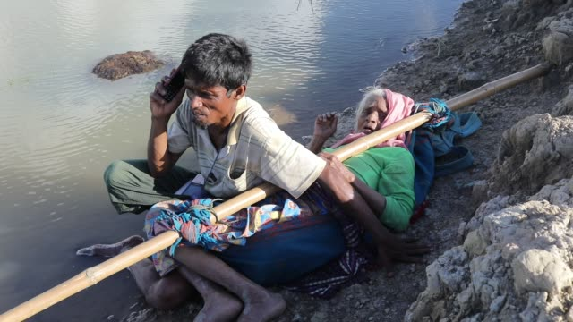 after crossing the bangladesh myanmar naf river border myanmar rohingya old woman takes rest and talk over a mobile phone in myanmar at palongkhali... - cox basar stock-videos und b-roll-filmmaterial