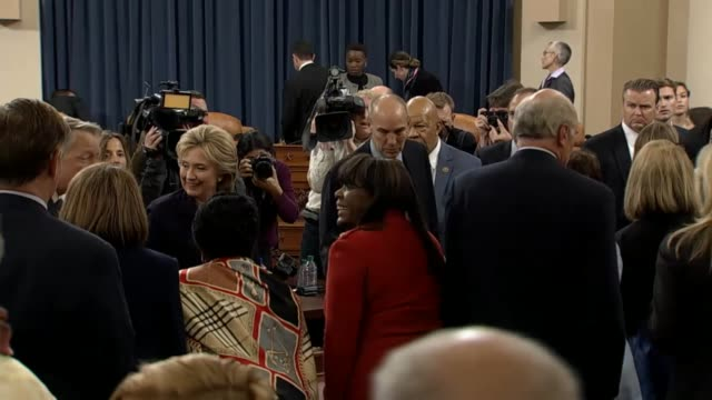 After eleven hours of testimony Former Secretary of State Hillary Clinton leaves the hearing room amid the clicks of cameras