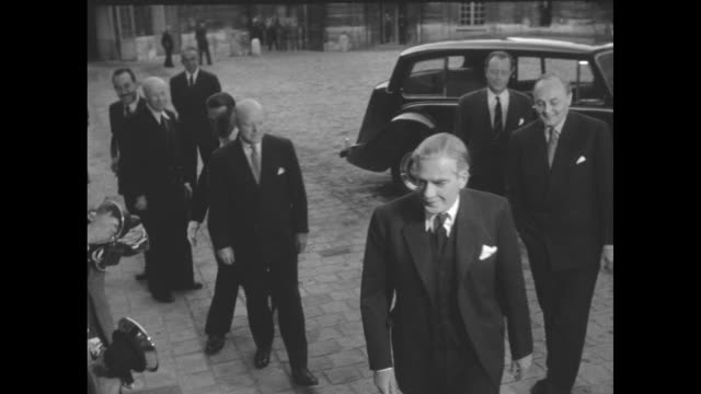 After getting out of limousine British Foreign Secretary Anthony Eden walks into building / Eden French Prime Minister Pierre Mendes France and US...