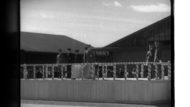 After his motorcade arrives at the Army and Air Force Academy Emperor Hirohito is welcomed by instructors and cadets then watches graduates receive...