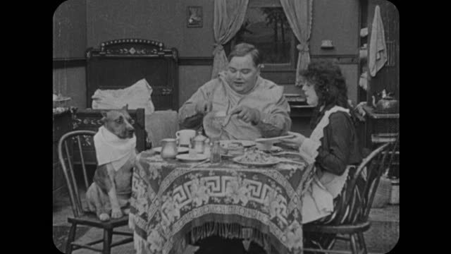 1916 after laughing at drink-stealing dog, man (fatty arbuckle) and wife (mabel normand) sit down to eat - napkin stock videos & royalty-free footage