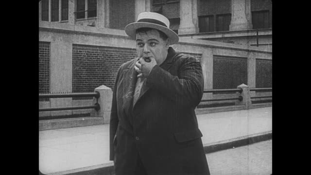 1917 after letting his car crash into crowd, man (fatty arbuckle) calls his car back to him like a dog - trillerpfeife stock-videos und b-roll-filmmaterial