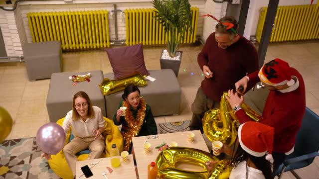 vidéos et rushes de après une longue journée de travail, un groupe moderne et diversifié d'entrepreneurs décorant l'espace de travail pour une fête du nouvel an - after work