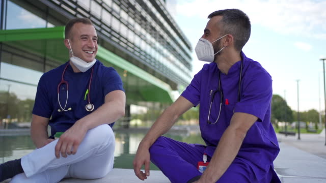after long shift of corona virus patient care ,doctors using a coffee break for some relaxation - fare una pausa video stock e b–roll