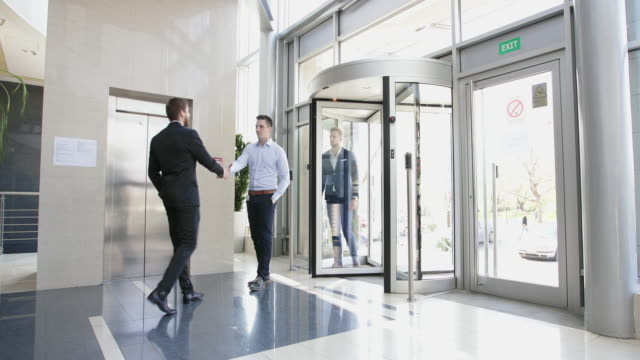 after meeting in the office lobby group of businessmen walking into elevator - entering stock videos & royalty-free footage