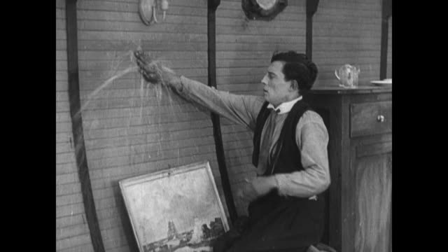 1921 After nailing hole in boat wall, man (Buster Keaton) nails pancake over leak to stem flow