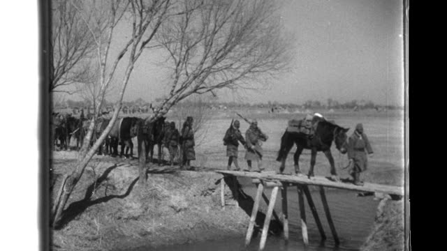 After Nationalist Chinese soldiers occupy a rural area Imperial Japanese soldiers of the China Expeditionary Army ford a creek and supported by...