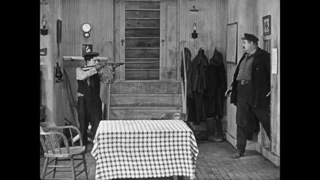 1923 after pointing gun at his captain (joe roberts) cabin boy (buster keaton) walks rifle into sea to shoot a fish - 1923 stock videos & royalty-free footage