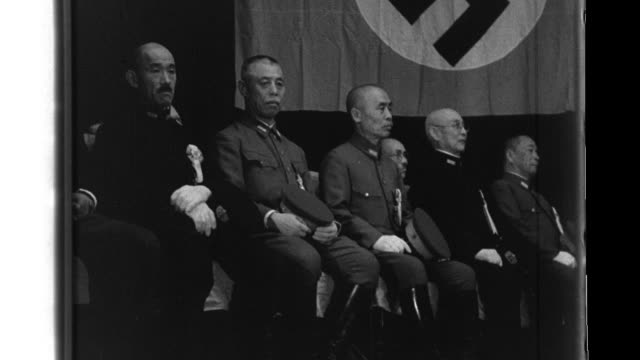 After Prime Minister Hideki Tojo delivers a speech from a platform with Italian and German ambassadors at Hibiya Public Hall the German Ambassador...