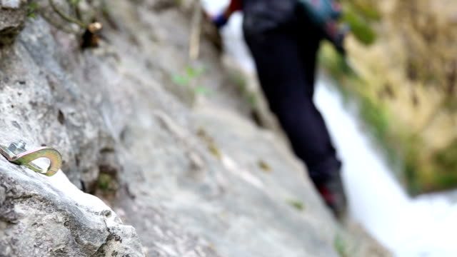 after putting a bolt on a rock , climber is moving on