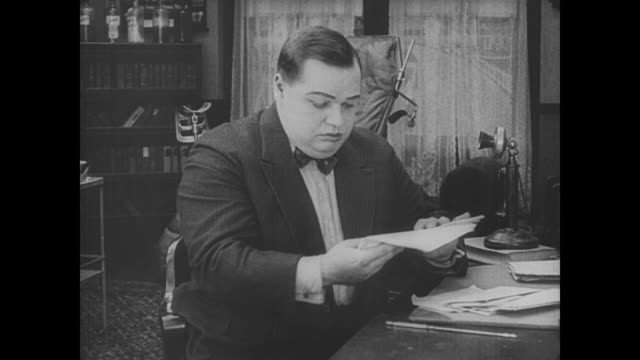stockvideo's en b-roll-footage met 1917 after reading a morbid request from local funeral home, upset man (fatty arbuckle) throws all his mail in the trash - post