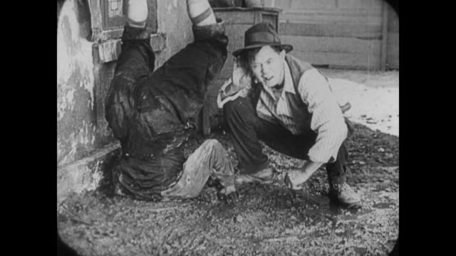 1920 After release from water barrel, upside down man (Buster Keaton) is pulled from mud by determined guilty father