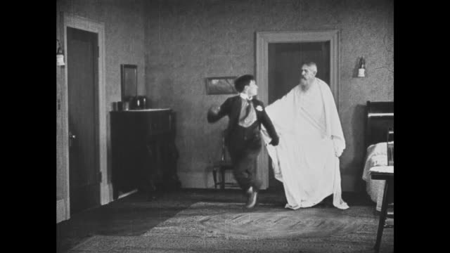 1921 After shaking hands with mouse, scared man (Buster Keaton) gets stuck running in circles with bed-sheeted Father Time