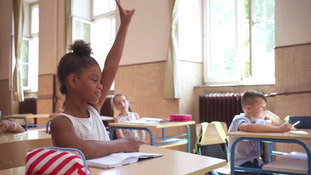 after she know the answer to teacher question smart female pupil raising her hand to answer it - first day of school stock videos & royalty-free footage