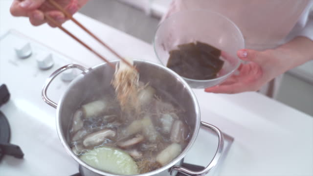 after simmering, scooping ingredients from broth - anchovy stock videos & royalty-free footage