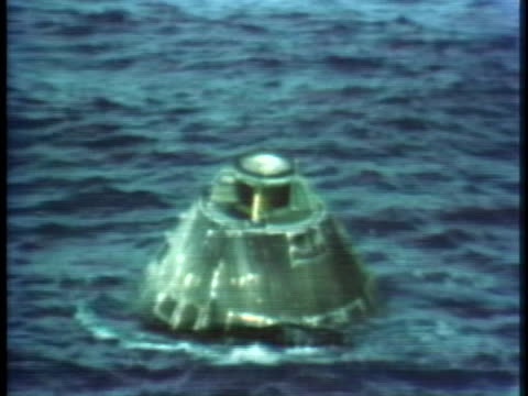 after splashdown, a helicopter flies over the apollo 13 spacecraft as it floats on the waters of the south pacific. - splashdown stock videos & royalty-free footage