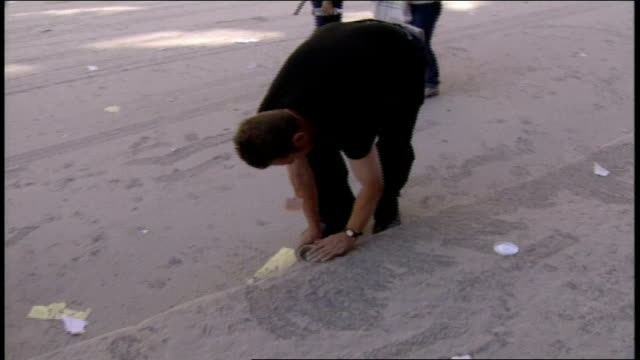 vídeos y material grabado en eventos de stock de after the collapse of the world trade center towers, a man on the street is scooping dust from the heavily coated street into a cup. - 2001
