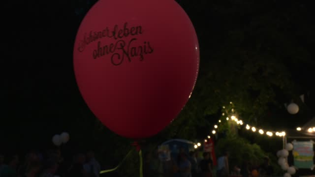 """after the counter-demonstration, the remaining demonstrators gather to a concert, a protester holds a balloon with the inscription """"live better... - links platz stock-videos und b-roll-filmmaterial"""