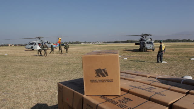 after the devastation of the january 12, 2010 earthquake.american helicopters bringing in us food and water supplies. - haiti stock-videos und b-roll-filmmaterial