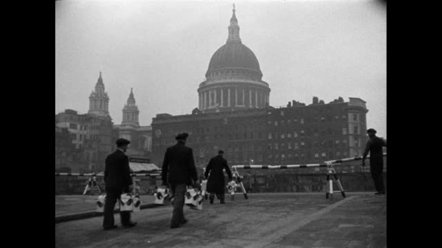 stockvideo's en b-roll-footage met montage after the war, lighting restrictions are eased as workers are tending to streetlights near st. paul's cathedral / london, england, united kingdom - 1946