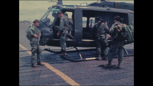 After their prisoner is escorted to a hospital members of the aero rifle platoon who wounded and captured him get their gear out of the Huey...